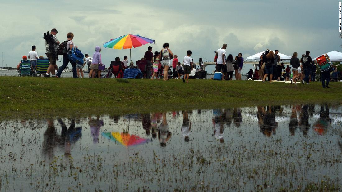 Le persone che si erano radunate per lanciare il lancio di SpaceX mercoledì lasciano Marina Park a Titusville, in Florida, dopo che è stato lavato.