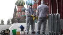 Persone con equipaggiamento protettivo che disinfetta la Piazza Rossa a Mosca.
