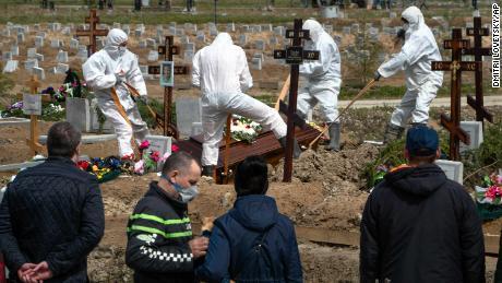 I becchini seppelliscono una vittima di COVID-19 mentre la famiglia e gli amici sono a distanza di sicurezza, in un cimitero di Kolpino, fuori San Pietroburgo, venerdì.