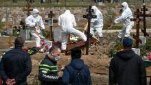Vecchi scavatori seppelliscono una vittima di COVID-19 mentre famiglia e amici sono a distanza di sicurezza, in un cimitero di Kolpino, fuori San Pietroburgo, venerdì.