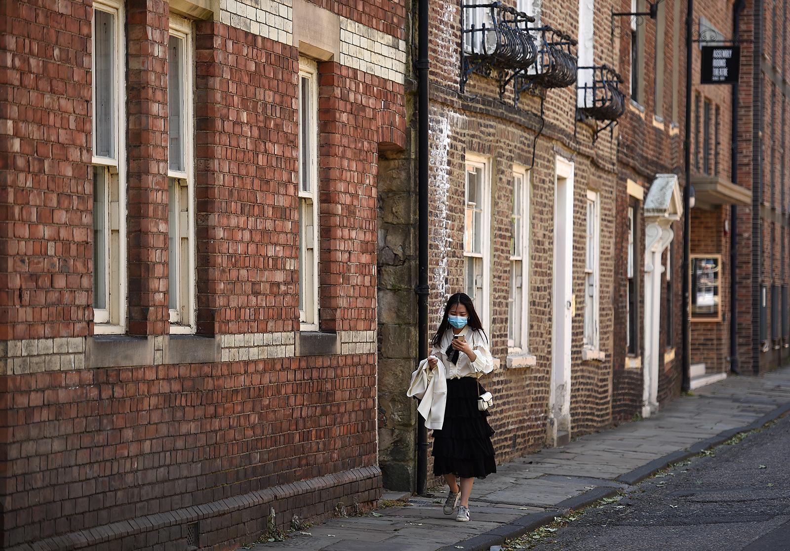 Una donna con una maschera per il viso cammina per una strada a Durham, nell'Inghilterra nord-orientale, il 25 maggio.