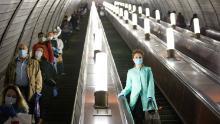 Martedì, persone con maschere e guanti su una scala mobile della metropolitana di Mosca.