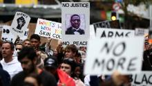 I manifestanti marciano per Queen Street ad Auckland, in Nuova Zelanda, lunedì.