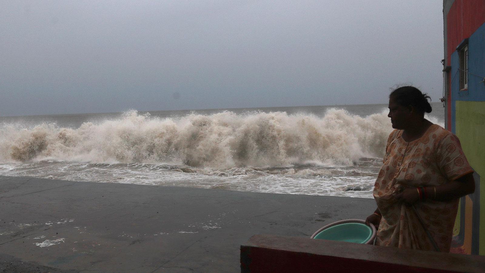 Una donna osserva le onde rotolare giù dalle rive del Mar Arabico a Mumbai, in India, il 3 giugno.