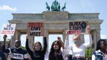 La gente partecipa a una manifestazione contro il razzismo di fronte alla Porta di Brandeburgo a Berlino domenica.